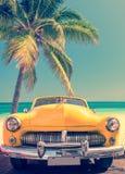 在一个热带海滩的经典汽车与棕榈树,葡萄酒样式 免版税库存图片