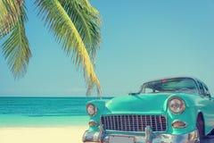 在一个热带海滩的经典汽车与棕榈树,葡萄酒过程 库存图片
