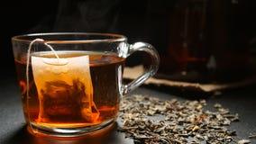 在一个热的茶杯的茶包在桌上 免版税库存图片