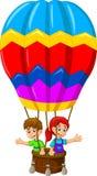 在一个热空气气球的滑稽的两个孩子动画片飞行 免版税库存照片