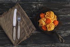 在一个煎锅的意粉用在黑土气背景的蕃茄 老叉子和刀子在一张亚麻布餐巾 顶视图 免版税库存图片