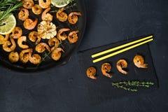 在一个煎锅的油煎的国王大虾在与黄色筷子的黑背景 库存照片