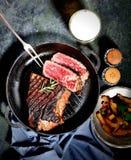 在一个煎锅的油煎的牛排用迷迭香、烤土豆、叉子、瓶子用香料和啤酒在黑暗的背景 库存照片