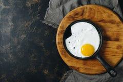 在一个煎锅的煎蛋在切板,黑暗的土气背景,顶视图,拷贝空间 免版税图库摄影