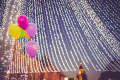 在一个照明设备帐篷下的五颜六色的气球在圣诞节市场上 免版税库存照片