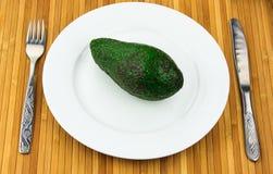 在一个牌照的鲕梨有刀叉餐具的 免版税库存照片