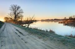 在一个狂放的池塘的岸的路在一个村庄旁边的在日出期间在秋天早晨 图库摄影