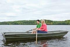 在一个独木舟的二个人骑马在湖 免版税图库摄影