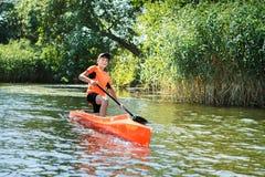 在一个独木舟的男孩划船在河 免版税图库摄影