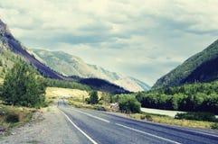 在一个狭窄的山谷的高速公路路沿河, woodla 免版税图库摄影