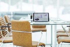 在一个现代办公室打开有财政图的便携式计算机在与经理的桌上 免版税库存照片