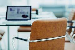 在一个现代办公室打开有财政图的便携式计算机在与经理的桌上 库存图片
