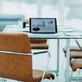 在一个现代办公室打开有财政图的便携式计算机在与经理的桌上 库存照片