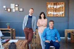 在一个现代办公室的微笑的小组买卖人 库存照片