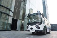在一个现代大厦旁边的一辆逗人喜爱的熊猫公共汽车 免版税库存照片