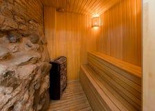 在一个现代天蒸汽浴、岩石墙壁和长木凳里面对si 库存照片