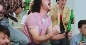 在一个现代房子小组朋友多种族观看非常情感足球赛他们愉快首先庆祝 股票视频
