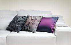 在一个现代沙发的三个装饰枕头 免版税库存图片