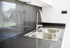 在一个现代设计的一个双重碗不锈钢厨房水槽 免版税库存照片