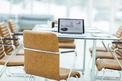 在一个现代办公室打开有财政图的便携式计算机在与经理的桌上 免版税库存图片