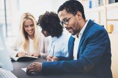 在一个现代办公室的三个年轻工友 供以人员佩带的玻璃,夹克和在文件的制造笔记 水平,蓝色 库存照片