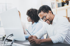 在一个现代办公室的三个年轻工友 白色衬衣的非裔美国人的人微笑在工作场所的 水平,蓝色 库存照片