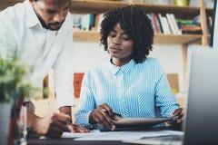 在一个现代办公室的两个年轻商人 黑人谈论与同事新的项目 水平 库存照片