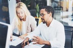 在一个现代办公室的两个年轻工友 供以人员佩带的玻璃和谈论与妇女新的项目 水平,迷离 免版税库存照片