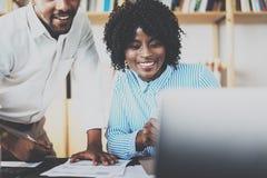 在一个现代办公室的两个年轻工友 谈论非洲黑人的商务伙伴新的起始的项目 免版税库存图片
