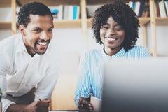 在一个现代办公室的两个年轻工友 非洲黑人商务伙伴使用膝上型计算机的和谈论新 库存图片