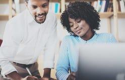 在一个现代办公室的小组年轻工友 使用膝上型计算机和谈论的非洲黑人商务伙伴 免版税库存照片
