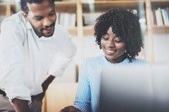 在一个现代办公室的小组年轻工友 使用膝上型计算机的非洲黑人企业同事和 图库摄影