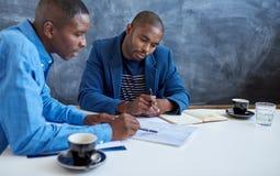 在一个现代办公室的年轻非洲商人 库存图片