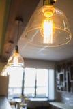 在一个现代咖啡馆-舒适内部的白炽灯 免版税库存照片