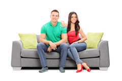 在一个现代沙发供以座位的年轻夫妇摆在 免版税库存照片