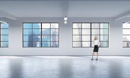 在一个现代顶楼露天场所站立一名全长妇女的正面图正式衣裳的 免版税库存图片