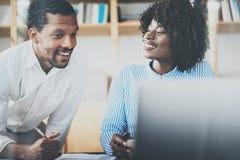 在一个现代coworking的演播室的小组两个年轻工友 使用膝上型计算机的非洲黑人商务伙伴 免版税图库摄影