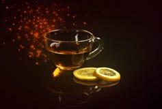 在一个玻璃杯子和柠檬切片的茶在黑暗的背景 免版税图库摄影