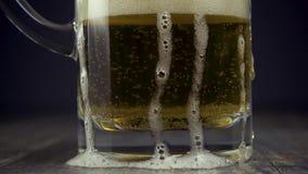 在一个玻璃杯子的慢动作低度黄啤酒在一个灰色背景特写镜头 股票录像