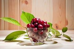 在一个玻璃杯子的成熟水多的樱桃木表面上 库存照片