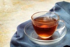 在一个玻璃杯子的新近地酿造的红茶,在a的通入蒸汽的热的饮料 库存图片