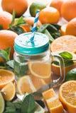 在一个玻璃杯子的新鲜的柠檬水有一个盒盖和一支一次性管的在果子的背景 库存照片