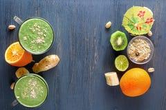 在一个玻璃杯子的新鲜的绿色圆滑的人在与蔬菜、水果和燕麦氯的一张木桌上在一张木桌上 库存图片
