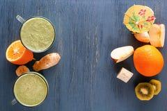 在一个玻璃杯子的新鲜的绿色圆滑的人在与蔬菜和水果的一张木桌上在一张木桌上 免版税图库摄影