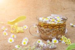 在一个玻璃杯子的甘菊茶有在一块粗麻布的铁框架的与菩提树开花 库存图片