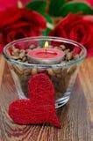 在一个玻璃杯子的红色蜡烛用咖啡豆和装饰重点 免版税图库摄影