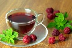 在一个玻璃杯子的莓茶 在背景的新鲜的莓 免版税库存图片
