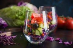 在一个玻璃杯子的被切的新鲜蔬菜 免版税图库摄影