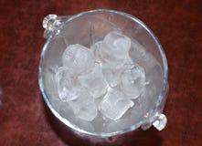 在一个玻璃桶的冰块在一张木桌上 库存照片