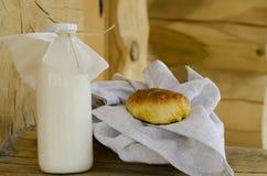 在一个玻璃瓶和一块玻璃的新鲜的牛奶,在一张木桌上的饼旁边 健康有机产品的概念 生锈的样式 免版税库存图片